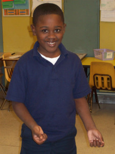 A smiling student during a classroom residency at Medgar Evans school in Chicago, IL.